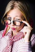 picture of cheeky  - Cheeky Female Business Geek Showing A Naughty Wink With Pink Pout Whilst Pulling Down On Glasses In A Depiction Of Business Trickery - JPG