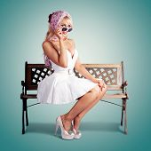 image of stereotype  - Classic Fashion Portrait Of A American Blond Beauty Sitting On A Park Bench Wearing Fashionable Headscarf Sunglasses And White Retro Dress - JPG