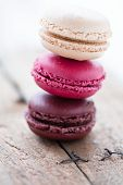 stock photo of french pastry  - Closeup of stack of three different flavoured macaroons on wooden table - JPG