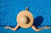 stock photo of sunbathing  - Woman in hat relaxing at the pool - JPG