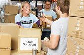 stock photo of poverty  - Volunteers Collecting Food Donations In Warehouse - JPG