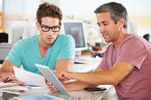 stock photo of spectacles  - Two Men Using Tablet Computer In Creative Office - JPG