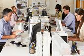 stock photo of fifties  - Team Working At Desks In Busy Office - JPG