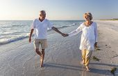 Happy senior man and woman couple walking and holding hands on a deserted tropical beach with bright