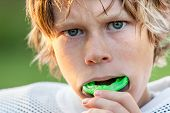 stock photo of adolescent  - Boy putting in his mouth guard - JPG
