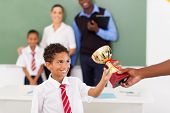 image of classmates  - elementary school boy receiving a trophy in classroom with teachers and classmate - JPG