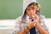 stock photo of teen smoking  - bad high school teen boy lighting cigarette in classroom - JPG