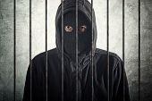 stock photo of scumbag  - Arrested burglar concept thief with balaclava caught and arrested put behind bars - JPG