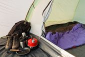 picture of sleeping bag  - Interior view of a dome tent set up for camping with various equipment and sleeping bag inside inner compartment