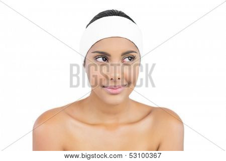 Pleased nude brunette with hairband looking away on white background