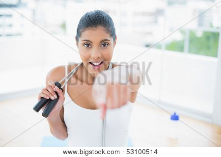 Excited toned brunette sitting on floor with skipping rope in bright room
