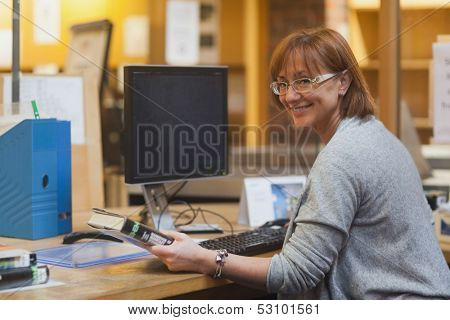 Smiling female librarian holding a book standing behind the desk looking at camera