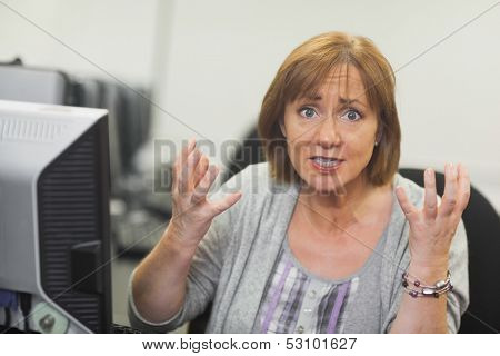 Outraged mature student sitting in front of computer looking at camera