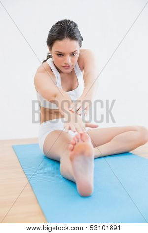 Full length of a toned young woman doing the hamstring stretch on exercise mat in fitness studio