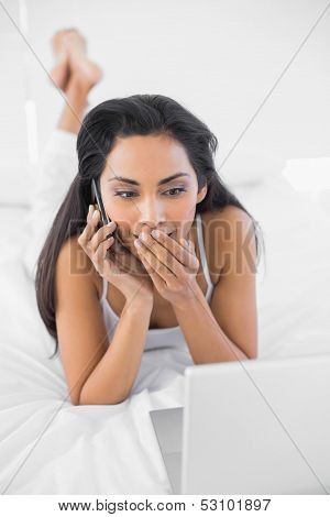 Astonished natural woman phoning while using her notebook lying on bed