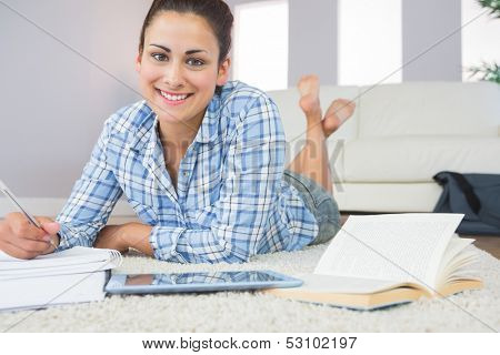 Portrait of joyful pretty student lying on the floor doing assignments in the living room