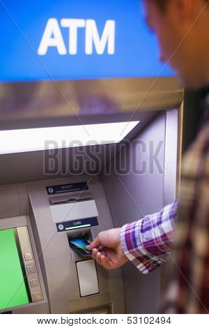 Casual student withdrawing cash at an ATM