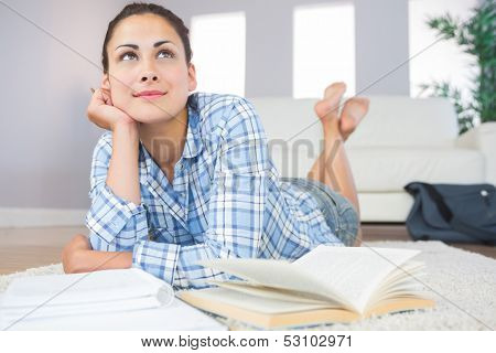 Gorgeous slender student lying thoughtful on the floor in the living room doing assignments