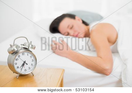 Blurred young woman sleeping in bed with alarm clock on bedside table in bedroom