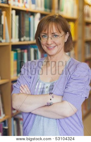 Mature female librarian posing in library with crossed arms looking at camera