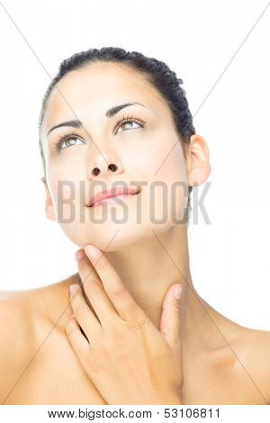 Front view of day dreaming beautiful woman looking upwards touching her throat