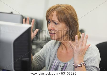 Annoyed mature woman working on computer in computer room