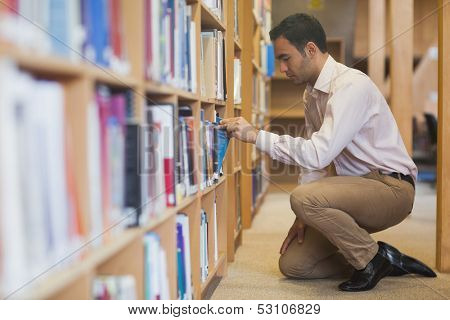 Handsome casual man cowering in front of bookshelves taking a book off a shelf