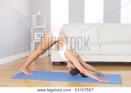Fit slim woman practicing yoga pose for stretching her body on exercise map in her living room