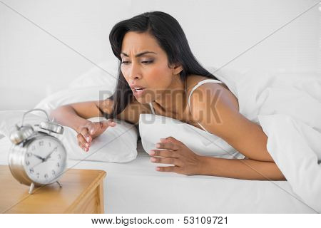 Attractive upset woman lying under the cover on her bed in bright bedroom