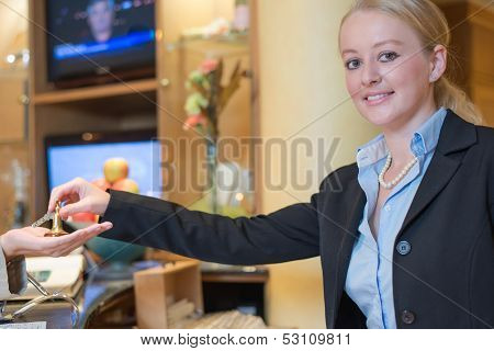 Smiling Receptionist Handing Over Room Keys