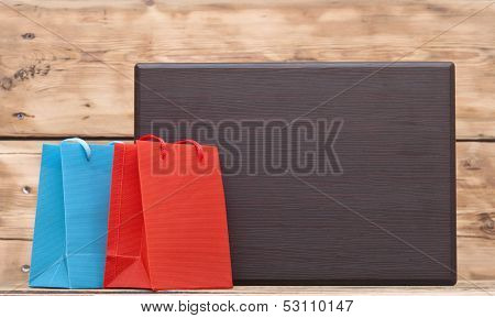 colorful shopping bags and blank wood plate with copy space for your text,
