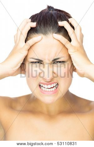 Front view of outraged brunette woman looking at camera grabbing her hair