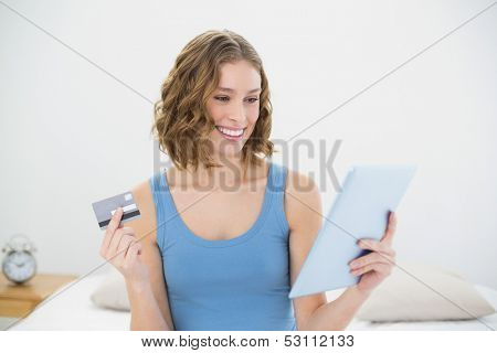 Gorgeous woman holding her tablet and debit card sitting on her bed in the bedroom
