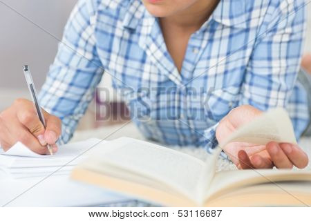 Mid section of young female student doing assignments while lying on the floor in the living room