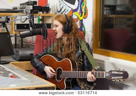 Happy beautiful singer recording and playing guitar in studio at college