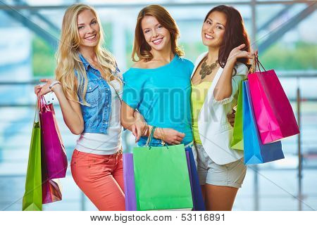 Portrait of three happy girls in smart casual holding paperbags