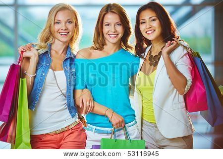 Portrait of three happy girls with paperbags looking at camera