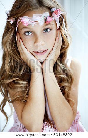 Portrait of beautiful little girl wearing floral wreath