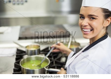 Young cheerful chef stirring sauce in professional kitchen