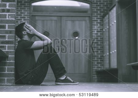 Unhappy handsome student in pain having a headache in school