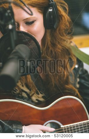 Content beautiful singer recording and playing guitar in studio at college