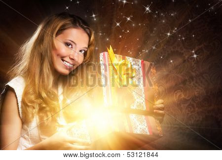 Young, happy and emotional teenage girl opening the magical Christmas present box