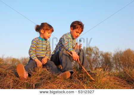 Little Girl And Boy With Bottle And Stick Sit On Grass