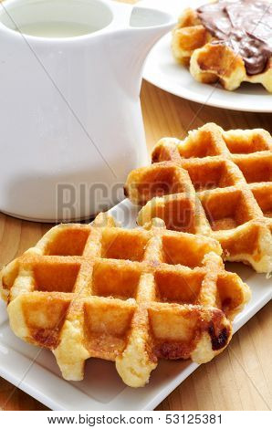a pot with milk and some waffles in a plate, on a wooden table