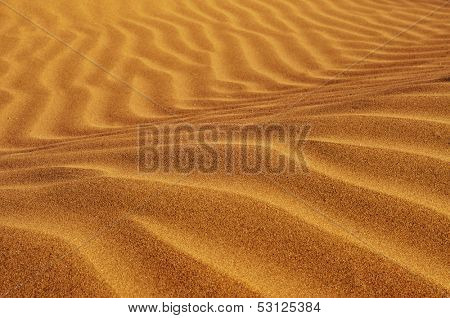 closeup of sand with a wavy pattern because the wind