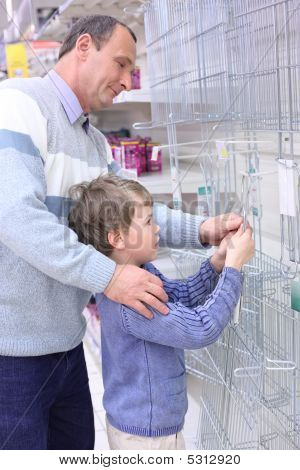 Elderly Man With Boy In Store Hang Grill For Roasting On Wall