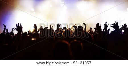 extreme wide-angel/panorama photo of a concert crowd in front of bright stage lights