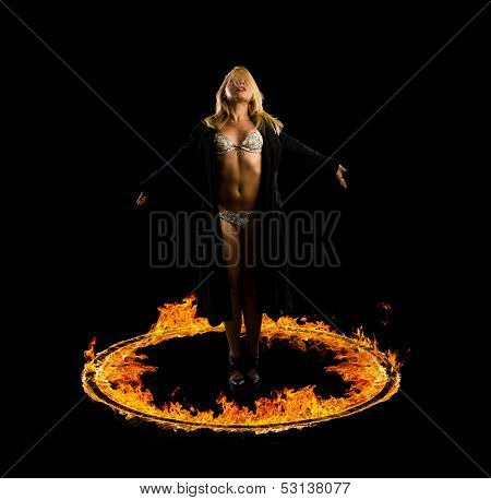 Woman in a circle of fire Blazing flames over black background