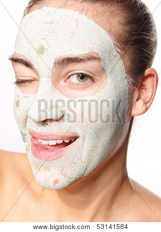 joyful woman in the mask with green clay