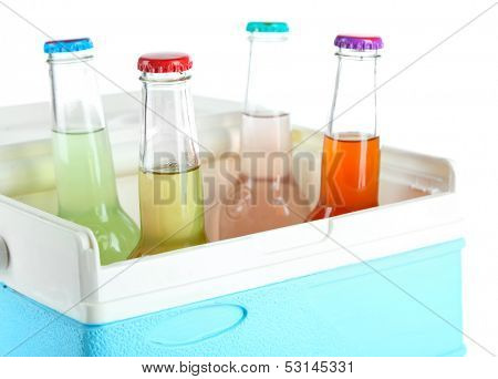 Drinks in glass bottles in mini fridge isolated on white